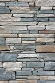 Ancient wall from slim granite brick. — Stock Photo