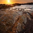 Sunset Across the Rocks Along a Pacific Beach - Stock Photo