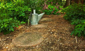 Trowel and Watering Can on the Garden Path — Stock Photo