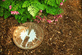 Sundial on Bark Mulch Next to Bleeding Hearts — Stock Photo