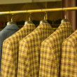 Foto Stock: Yellow Checkered Suits on Rack