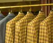 Yellow Checkered Suits on Rack — Stock Photo