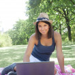 Young woman using laptop in park — Stock Photo #19479989