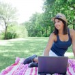 Stock Photo: Young woman using laptop in park