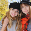 Portrait of two young women in autumn park - Stock Photo