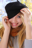 Young smiling girl in a hat hiding eye — Stock Photo