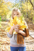 Teen girl holding a bunch of leaves in autumn park — Stock Photo