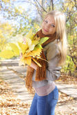 Girl holding a bunch of leaves in park — Stock Photo