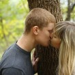 Autumn portrait of kissing young couple near the wood — Stock Photo