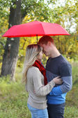 Young couple man and woman hugging with umbrella autumn — Stock Photo