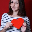 Woman holding Valentine heart on red background — Stock Photo