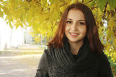 Brunette woman with black scarf in the autumn park. — Stock Photo