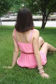 Morena joven sentado en un pasto verde — Foto de Stock