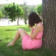 Sad young woman sitting in the park. — Stock Photo #34912239