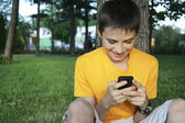 Young man holding a smartphone and text message park — Stock Photo