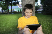Boy teenager play Tablet PC outdoor summer park — Stock Photo