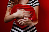 Woman hold in hands heart shaped red balloon — Stok fotoğraf
