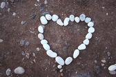 White heart of stone on sand background — Stock Photo