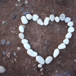 White heart of stone on sand background — Zdjęcie stockowe