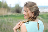Spring portrait smiling young girl in profile with hair in braid — Stock Photo