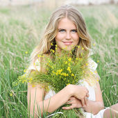 Young blonde happy girl  sitting field with  flowers spring — Stock Photo