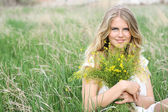 Young blonde smiling happy girl field with  flowers spring — Stock Photo