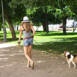 Young woman walking her beagle dog in the green park — Stock Photo #49729657