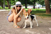 Happy young woman playing with Beagle dog outdoors . funny shot — Stock Photo