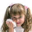 Little girl blowing on a feather - Stock Photo