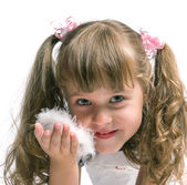 Little girl blowing on a feather — Stock Photo