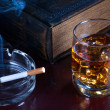 Whisky, cigarette and an old book nearby — Stock Photo