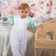baby girl standing near  the chair — Stock fotografie