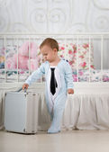 Baby boy stands with a suitcase — Stock Photo