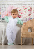 Baby girl standing near the chair — Stock Photo