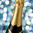 Glasses and bottle of champagne, serpentine isolated on a holiday bokeh background. — Stock Photo