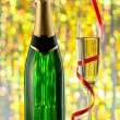 Glasses and bottle of champagne, serpentine isolated on a holiday bokeh background. — Stock Photo #36367597