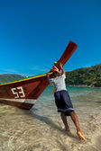 Fisherman pushes longtail boat — Stock fotografie