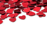 Valentines decoration of red confetti hearts against white background with bokeh — Stock Photo