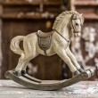 Vintage old rocking horse on a wooden background — Stock Photo #40966525