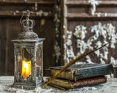 Vintage lamp for the candle and old books on wooden table — Photo