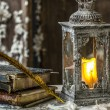 Vintage lamp for the candle and old books on wooden table — Stock Photo #41144413