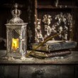 Vintage lamp for the candle and old books on wooden table — Stock Photo #41144449