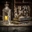 Vintage lamp for the candle and old books on wooden table — Stock Photo