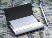 Business card holder and pen on the background of the new hundred dollars American — Stock Photo