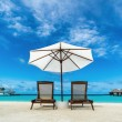 Beach lounger and umbrella on sand beach. Concept for rest, relaxation, holidays, spa, resort. — Stock Photo #49392335