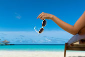 Young girl lying on a beach lounger with glasses in hand on the tropical island — Stock Photo
