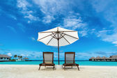 Beach lounger and umbrella on sand beach. Concept for rest, relaxation, holidays, spa, resort. — Stock Photo