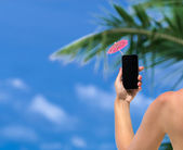 Woman hand showing mobile phone and cocktail umbrella on the sky in the background — Stock Photo
