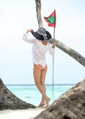 Glückliche junge Frau auf den Strand und Flagge Malediven — Stockfoto