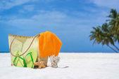 Summer beach bag with starfish,towel,sunglasses and flip flops on sandy beach — Stock Photo